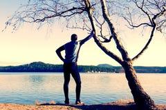 Silueta del hombre activo del deporte en polainas corrientes y de la camisa azul en el árbol de abedul en la playa Agua, isla y d Imagen de archivo libre de regalías