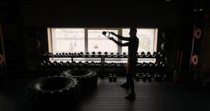 Silueta del hombre atlético que se resuelve con el fondo del negro del gimnasio de las pesas de gimnasia, hombre con pesas de gim metrajes