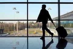 Silueta del hombre cerca de la ventana en aeropuerto Foto de archivo