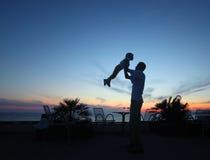Silueta del hombre con el niño en manos en puesta del sol foto de archivo