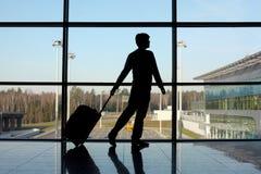 Silueta del hombre con equipaje cerca de la ventana Imagen de archivo libre de regalías