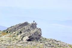 Silueta del hombre con estancia de la mochila en pico de la roca de bloques rectangulares Imagen de archivo libre de regalías
