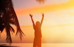 Silueta del hombre con sus manos para arriba en la puesta del sol Foto de archivo libre de regalías