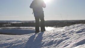 Silueta del hombre con una mochila que camina en un paisaje del invierno en las raquetas Extremo de la afición de la actividad de almacen de video