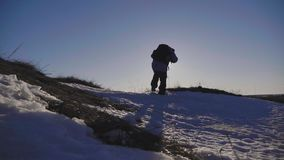 Silueta del hombre con una mochila que camina en un paisaje del invierno en las raquetas Senderismo con caminar los polos, cielo  almacen de metraje de vídeo