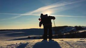 Silueta del hombre con una mochila que camina en un paisaje del invierno en las raquetas Senderismo con caminar los polos, cielo  almacen de video