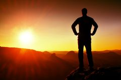 Silueta del hombre confiado y potente joven que se coloca con las manos en caderas, la mañana o el último día Sun con el espacio  imágenes de archivo libres de regalías