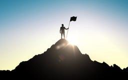 Silueta del hombre de negocios con la bandera en la montaña Foto de archivo libre de regalías