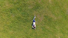 Silueta del hombre de negocios Cowering Chica joven que miente y que descansa sobre césped el día soleado en parque en hierba Sob almacen de metraje de vídeo