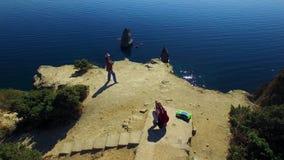 Silueta del hombre de negocios Cowering Dos turistas que toman las fotos en el acantilado de Fiolent del cabo almacen de video