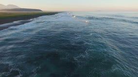 Silueta del hombre de negocios Cowering El volar a lo largo de la orilla del océano almacen de video