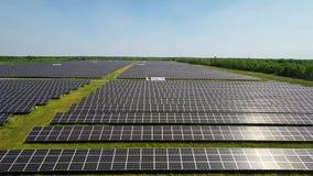 Silueta del hombre de negocios Cowering El volar sobre la planta de energía solar con el sol Los paneles solares y Sun Tiro aéreo metrajes