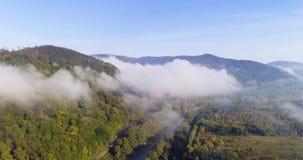 Silueta del hombre de negocios Cowering El volar sobre las altas montañas en nubes hermosas Tiro de la cámara aérea Ventile las n metrajes