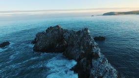 Silueta del hombre de negocios Cowering la cámara vuela alrededor de las rocas en los pájaros de mar en la isla La cámara enfoca
