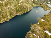 Silueta del hombre de negocios Cowering Lagos en las montañas Noruega imagenes de archivo