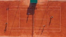 Silueta del hombre de negocios Cowering Los jugadores están jugando a tenis en corte anaranjada almacen de video