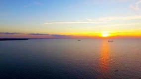 Silueta del hombre de negocios Cowering P?jaros que vuelan sobre el mar en la puesta del sol almacen de video