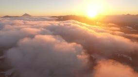 Silueta del hombre de negocios Cowering Puesta del sol El sol viene en las nubes detrás de las montañas almacen de video