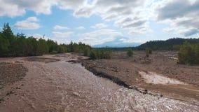 Silueta del hombre de negocios Cowering Río borroso en las montañas El camino fue lavado con agua metrajes