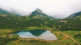 Silueta del hombre de negocios Cowering Reflexiones de la montaña en un lago Acercamiento cercano a la cascada por el dron almacen de metraje de vídeo