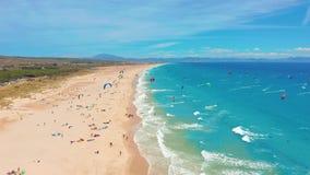 Silueta del hombre de negocios Cowering Una playa grande llenada de las personas que practica surf de la cometa en Tarifa, España metrajes