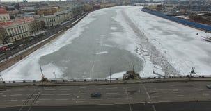 Silueta del hombre de negocios Cowering Vuelo a lo largo del río Neva en tiempo frío del revestimiento del invierno Puente sobre  almacen de video