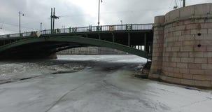 Silueta del hombre de negocios Cowering Vuelo a lo largo del río Neva en tiempo frío del revestimiento del invierno Puente sobre  almacen de metraje de vídeo