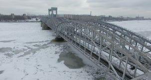 Silueta del hombre de negocios Cowering Vuelo a lo largo del río Neva en tiempo frío del revestimiento del invierno Puente sobre  foto de archivo libre de regalías