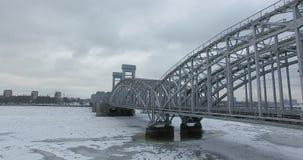 Silueta del hombre de negocios Cowering Vuelo a lo largo del río Neva en tiempo frío del revestimiento del invierno Puente sobre  fotos de archivo libres de regalías