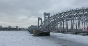 Silueta del hombre de negocios Cowering Vuelo a lo largo del río Neva en tiempo frío del revestimiento del invierno Puente sobre  fotografía de archivo