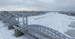 Silueta del hombre de negocios Cowering Vuelo a lo largo del río Neva en tiempo frío del revestimiento del invierno Puente sobre  fotos de archivo