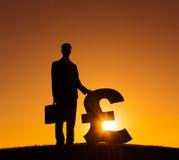 Silueta del hombre de negocios Holding Currency Sign Imágenes de archivo libres de regalías