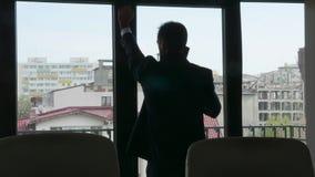 Silueta del hombre de negocios que habla en el teléfono metrajes