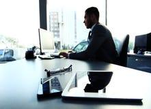 Silueta del hombre de negocios usando el ordenador portátil Imágenes de archivo libres de regalías