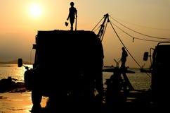 Silueta del hombre en el camión con el cielo de la puesta del sol Fotografía de archivo libre de regalías