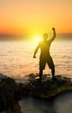 Silueta del hombre en el fondo del océano de la puesta del sol Imagenes de archivo