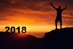 Silueta del hombre en el top de la montaña que mira la salida del sol y el 2018 Imagen de archivo
