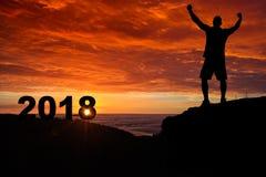 Silueta del hombre en el top de la montaña que mira la salida del sol y el 2018 Imagen de archivo libre de regalías