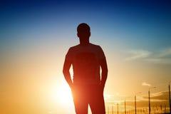 Silueta del hombre en fondo de la puesta del sol Fotografía de archivo