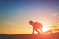 Silueta del hombre en la posición a correr en fondo de la puesta del sol Foto de archivo