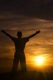 Silueta del hombre en montañas en la puesta del sol Foto de archivo