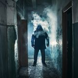 Silueta del hombre en pasillo espeluznante oscuro en nubes del humo del vapor o del vapor del vape, atmósfera del horror del mist imagenes de archivo