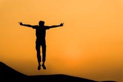 Silueta del hombre en salto feliz en el cielo anaranjado de la puesta del sol imagen de archivo