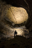 Silueta del hombre en una cueva oscura enorme Imagen de archivo