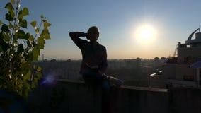 Silueta del hombre joven notas de esa lectura en la puesta del sol en el top del tejado almacen de metraje de vídeo