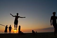 Silueta del hombre joven que equilibra en slackline en Foto de archivo