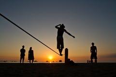 Silueta del hombre joven que equilibra en slackline en Imagen de archivo