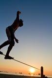 Silueta del hombre joven que equilibra en slackline en Fotografía de archivo