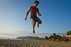 Silueta del hombre joven que equilibra en slackline en Foto de archivo libre de regalías