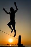 Silueta del hombre joven que equilibra en slackline en Imagen de archivo libre de regalías